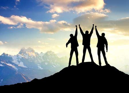 mountain peaks: Silhouette of the winners team Stock Photo