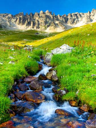 Fluss amond Steinen und Gras