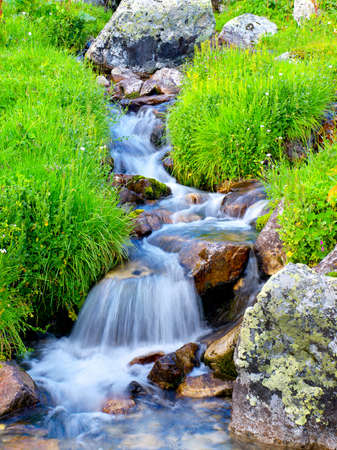 rivers mountains: River among stones and grass Stock Photo