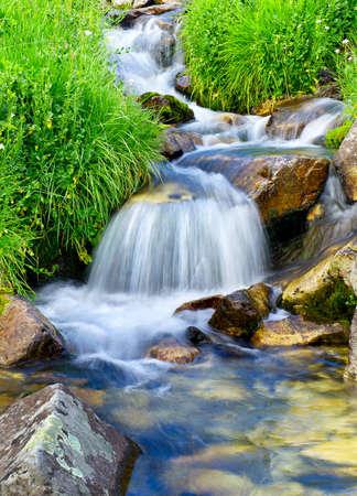 Fluss unter Steinen und Gras Standard-Bild