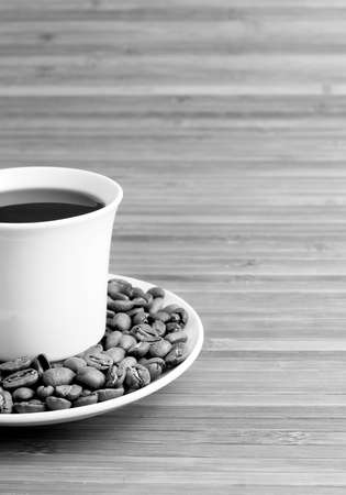 Monochrome coffee cup and coffee grains  Concept and idea photo