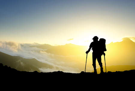 Silhouette of a tourist on the mountain top