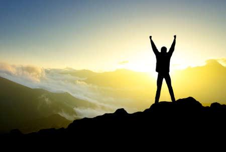 Silhouette von einem Gewinner auf dem Berggipfel Standard-Bild