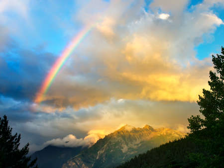 rainbow scene: Rainbow in the mountain valley after rain Stock Photo