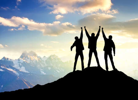Silhouettes of a champions on the mountain top Foto de archivo