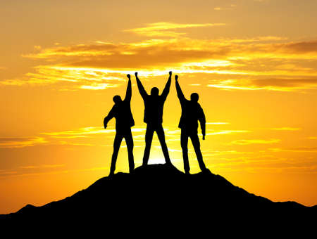 Silhouettes of a winners on the mountain top photo