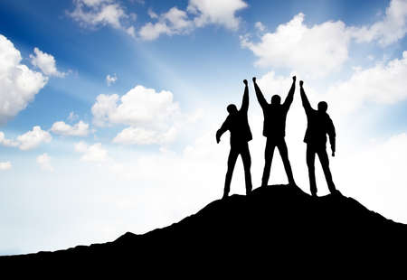 Silhouettes of a winners on the mountain top