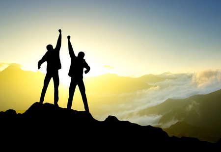 Silhouette of a winners on the mountain top Foto de archivo