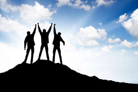 Silhouette of a winners team on the mountain top