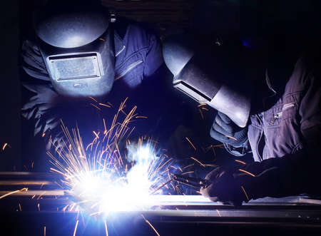 Welders team on industrial workplace