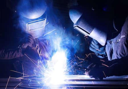 Welders team on industrial workplace