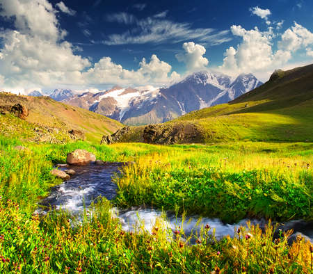 River on meadow amongst mountain valley
