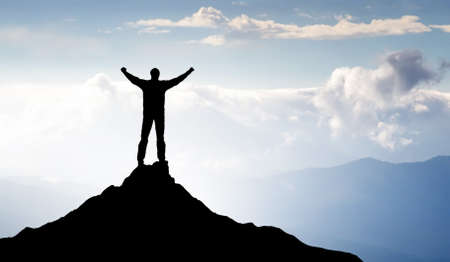 Silhouette of winner on mountain top