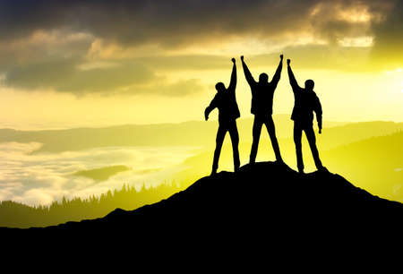 Silhouette of sport team on mountain top