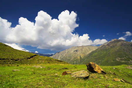 Field and clouds in mountain valley. Beautiful natural landscape photo