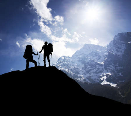 Silhouette of tourists on mountain peak. Sport and active life concept Standard-Bild