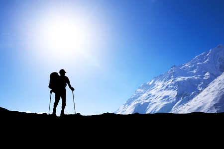 Silhouette of tourist on mountain peak. Sport and active life concept