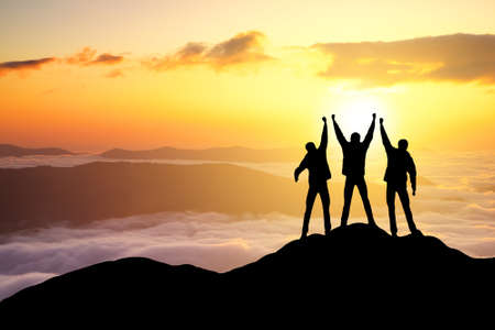 group search: Silhouettes of team on mountain peak. Sport and active life concept Stock Photo