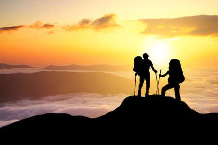 Silhouetten von Touristen-Team auf Berggipfel. Sport und aktives Leben-Konzept Standard-Bild