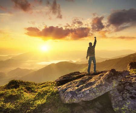 mochila de viaje: Silueta de un campeón en la cima de la montaña. Concepto de la vida activa