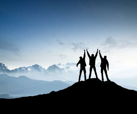 Silhouettes of team on mountain peak. Sport and active life concept 스톡 콘텐츠