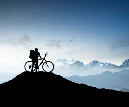 Silhouette of a bike tourist on mountain peak. Active life concept Foto de archivo