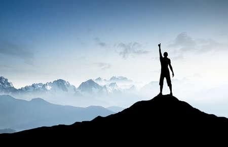 путешествие: Победитель силуэт на вершине горы. Спорт и активный образ жизни концепция