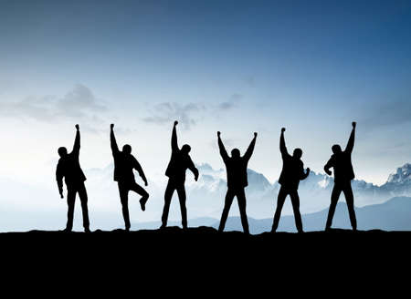 Silhouettes of team on mountain peak. Sport and active life concept Foto de archivo