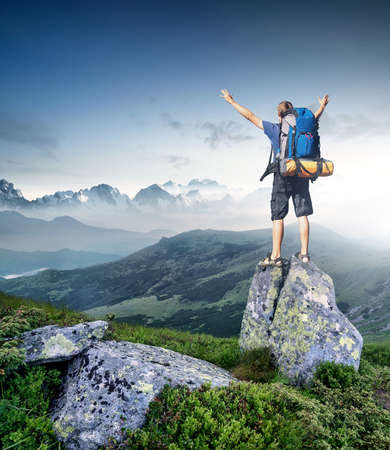 success man: Tourist on top of high peak. Sport and active life concept