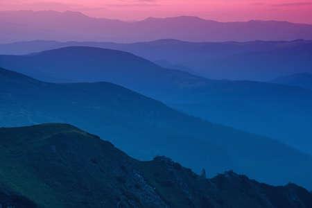 Hills lines in mountain valley during sunset. Natural summer mountain landscape Standard-Bild
