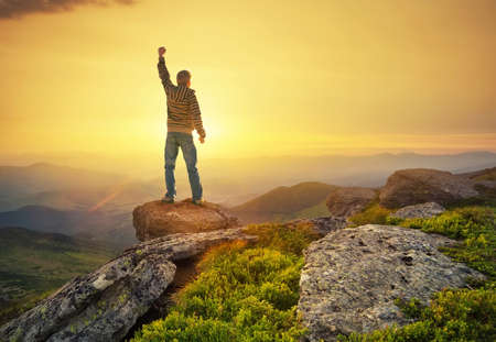 Silhouette of a champion on mountain peak. Active life concept Standard-Bild
