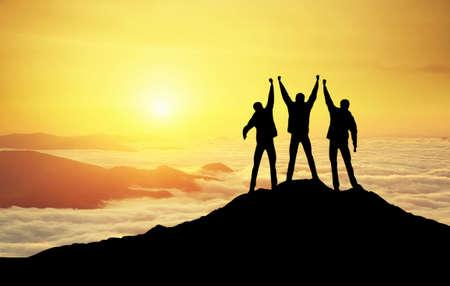 Silhouettes of Team auf Berggipfel. Sport und aktives Leben-Konzept Standard-Bild