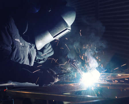 Welding and bright sparks. Concept and idea of hard job 스톡 콘텐츠