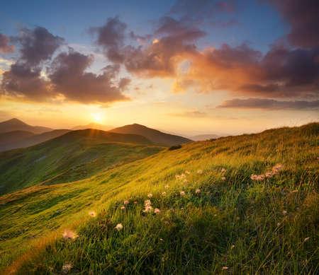 anochecer: Campo de la montaña durante la puesta del sol. Parajes naturales Foto de archivo
