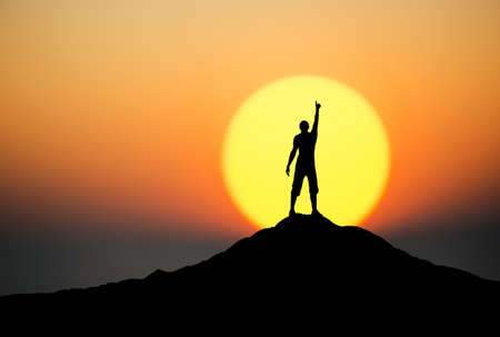 sunset clouds: Silhouette of a champion on mountain peak. Active life concept Stock Photo