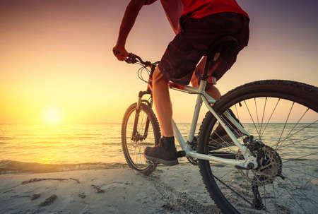 Fahren Sie mit dem Fahrrad auf dem Strand. Sport und aktiver Lebenskonzept