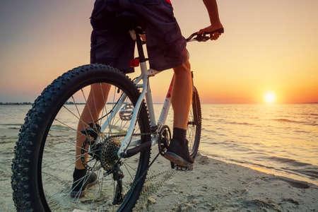 Ritje op de fiets op het strand. Sport en actieve leven concept Stockfoto