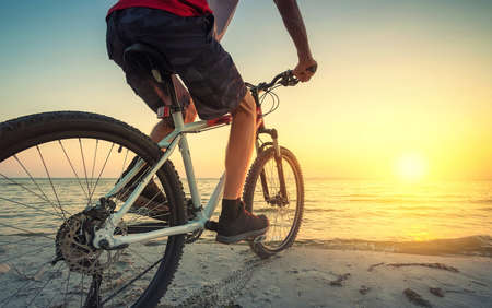 road cycling: Ride on bike on the beach. Sport and active life concept Stock Photo