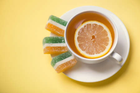mid afternoon: Tea with lemon and fruit jelly. Food and drink as a background