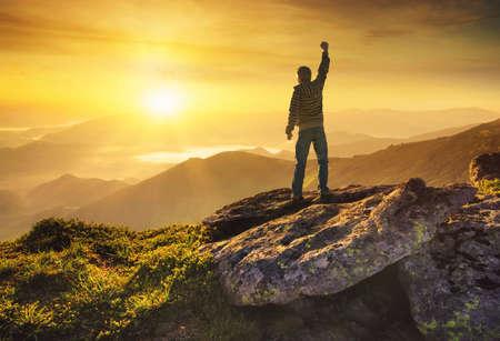 концепция: Победитель силуэт на вершине горы. Спорт и активный образ жизни концепция