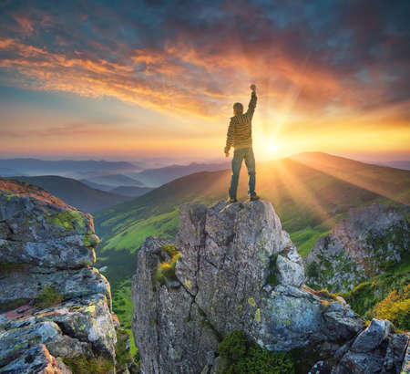 Silhouette of a champion on mountain peak. Active life concept Stock Photo
