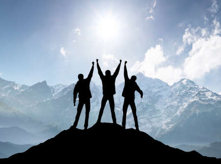 Silhouettes of team on mountain peak. Sport and active life concept Banco de Imagens - 53005347