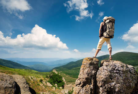 Tourist on the peak of high rocks. Sport and active life concept