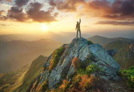 Silhouette of a champion on mountain peak. Active life concept Banco de Imagens