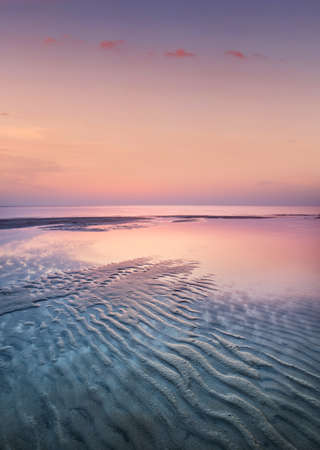 Sand on the seashore during sunset. Beautiful natural seascape in the summer time