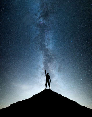 Silhouettes of team on mountain peak. Sport and active life concept on the night sky background  Banco de Imagens