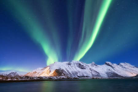 Aurora borealis on the Lofoten islands, Norway. Green northern lights above mountains. Night sky with polar lights. Night winter landscape with aurora and reflection on the water surface. Natural background in the Norway Imagens
