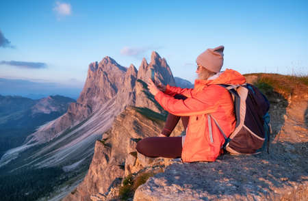Tourist make a photo by a phone on the high mountain top. Adventure and travel concept. People traveling in the mountains. Dolomite Alps, Italy. Stok Fotoğraf