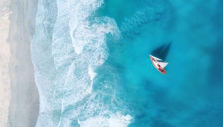 Yacht auf der Wasseroberfläche von oben. Türkisfarbener Wasserhintergrund von der Draufsicht. Sommerseelandschaft aus der Luft. Reisekonzept und Idee
