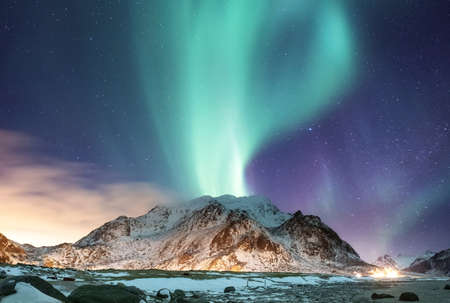 Aurora borealis on the Lofoten islands, Norway. Green northern lights above mountains. Night sky with polar lights. Night winter landscape with aurora and reflection on the water surface. Natural background in the Norway Standard-Bild - 112215968